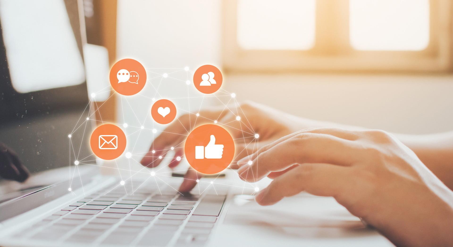 Ręce podczas pracy na laptopie, dookoła ikony mediów społecznościowych.