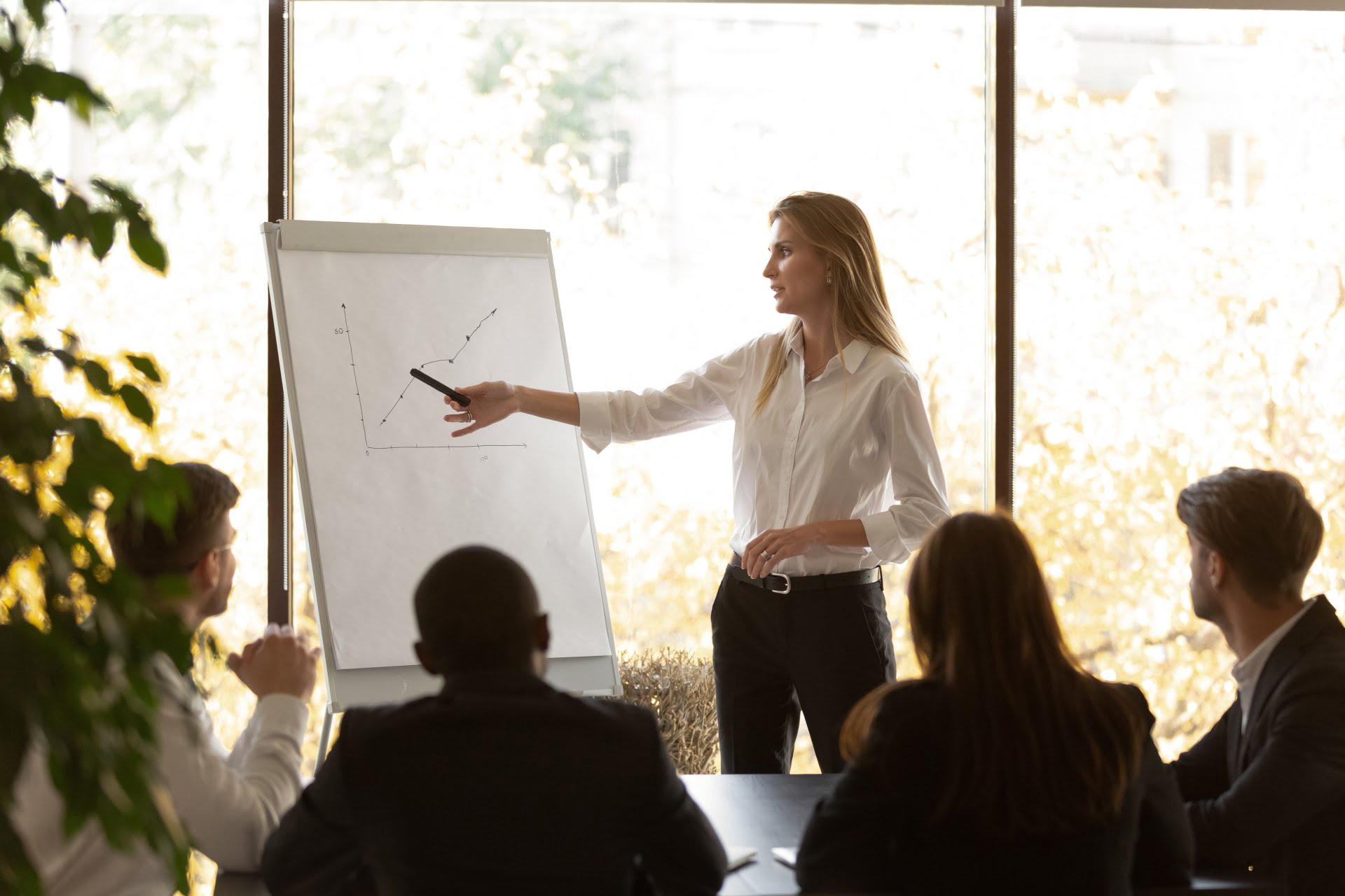 Kobieta analizująca wykres podczas spotkania handlowego.
